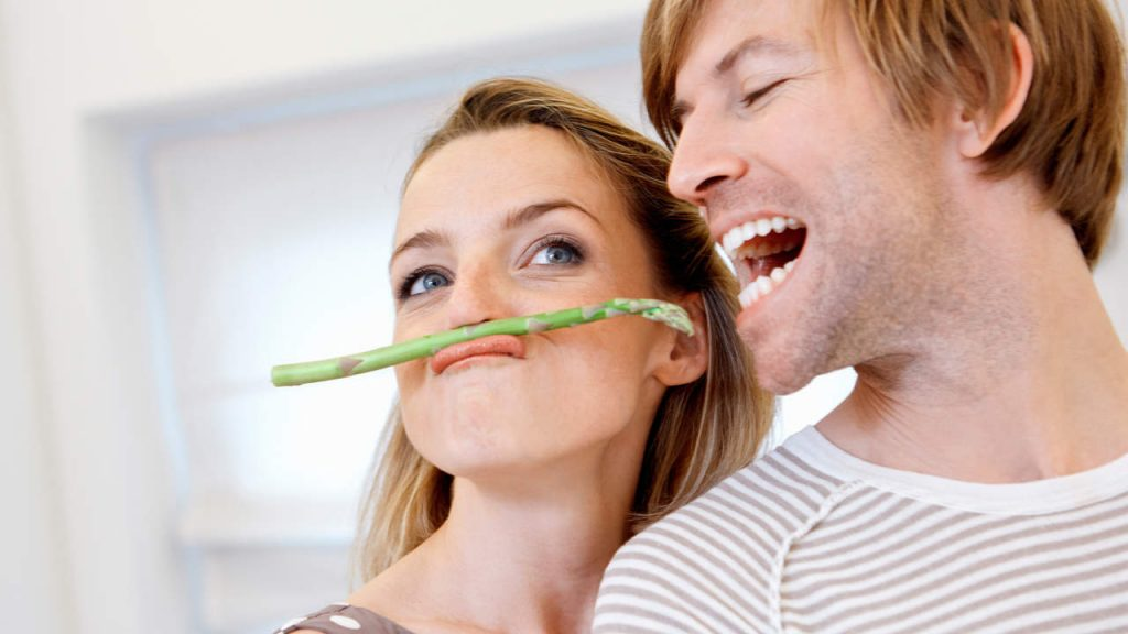 man and woman eating asparagus as an aphrodisiac
