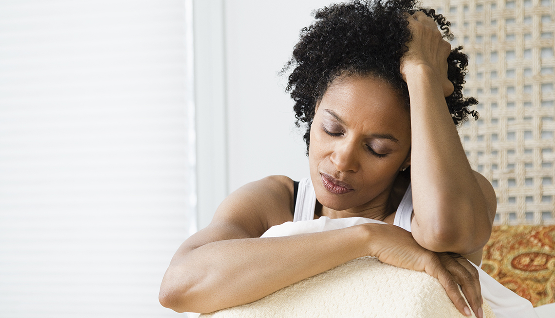 Mid adult woman sitting on the bed and suffering from a headache